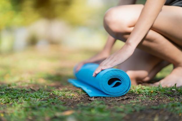 女性は公園でエクササイズヨガ、スポーツヨガのコンセプトを行うためにローリングヨガマットを使用しています