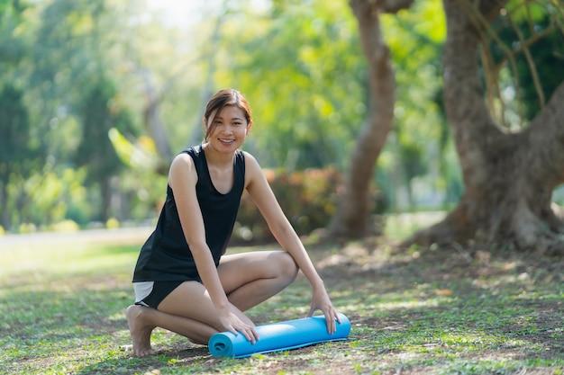 여성은 롤링 요가 매트를 사용하여 공원에서 운동 요가, 스포츠 요가 개념을 수행합니다.