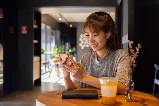 Women use smart phone in coffee cafe