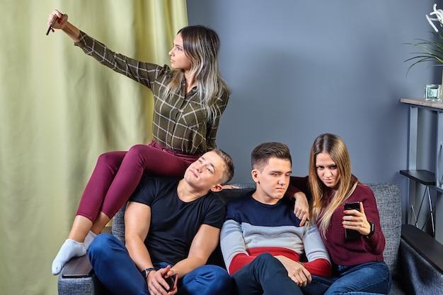여성은 스마트 폰을 사용하여 셀카를 찍고 남성이 지루하다는 메시지를 봅니다.