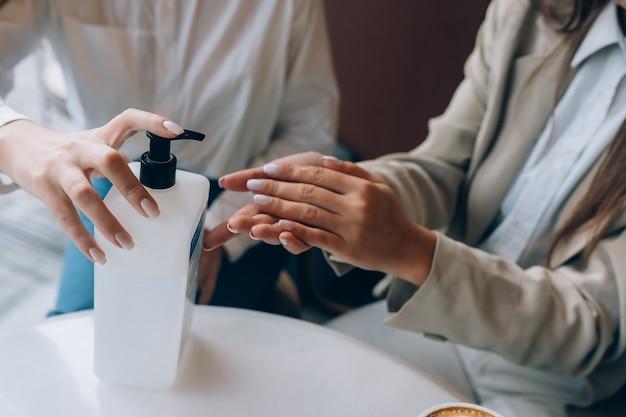 Женщины, использующие антибактериальный антисептик для дезинфекции в кафе. новые социальные правила после концепции пандемии.