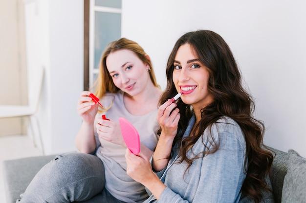 ソファーで化粧品を使用している女性