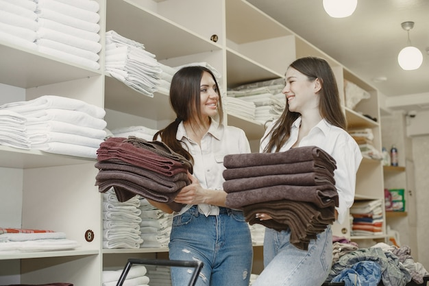 乾燥機を使用している女性。服を乾かす準備ができている若い女性。インテリア、dryindプロセスのコンセプト。