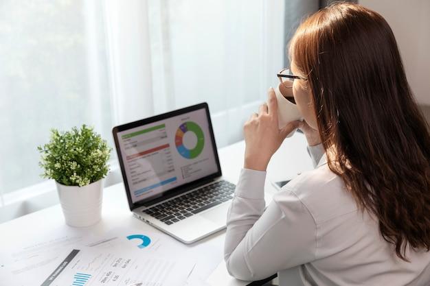 ホームオフィスでラップトップを使用してコーヒーを飲む女性、若い女性はビジネスの計画を立てています。