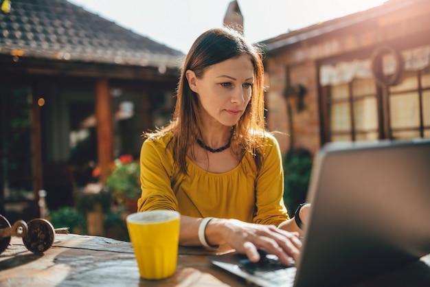 Women using laptop at backyard patio