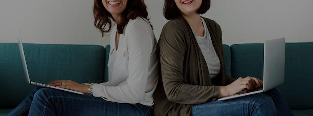 一緒にソファでノートパソコンを使用している女性