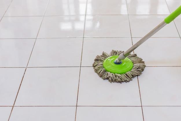 Женщины с помощью швабры моют грязный пол в доме.
