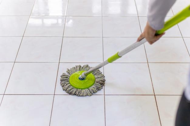 집안의 더러운 바닥을 청소하는 걸레를 사용하는 여성.