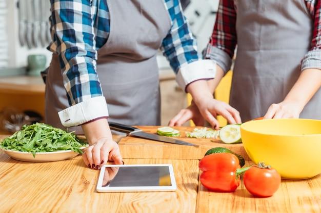 Женщины используют планшет, чтобы найти рецепт, стоя на кухне