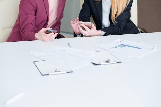 Женщины используют свои мобильные телефоны во время деловой встречи