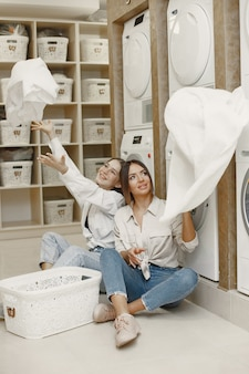 Women using washing machine doing the laundry. young girls ready to wash clothes. interior, washing process concept