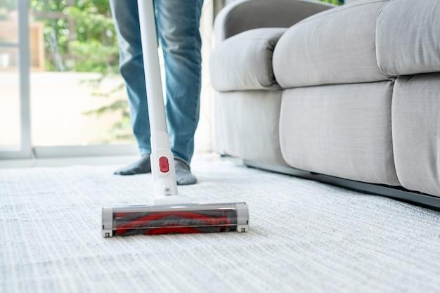 自宅でカーペットを掃除するワイヤレス掃除機を使用している女性