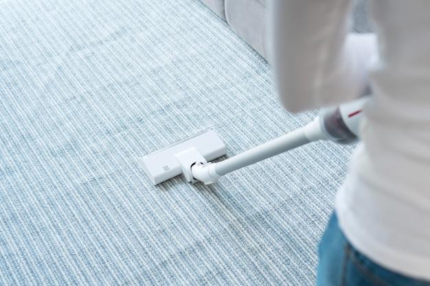 自宅のリビングルームでカーペットを掃除するワイヤレス掃除機を使用している女性。閉じる