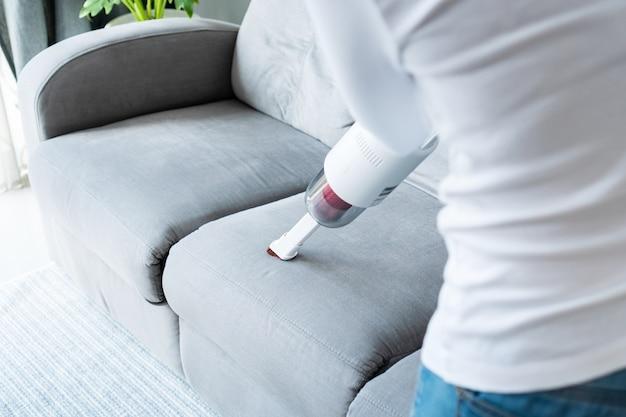 ワイヤレス掃除機クリーニングソファを使用している女性