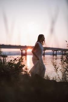 Женщины гуляют по берегу реки на закате молодая брюнетка в белом летнем платье гуляет по ...