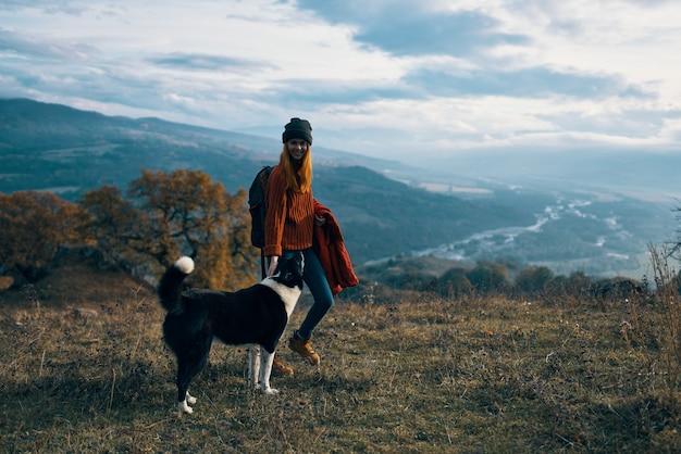 自然の風景の山で犬の隣を歩く女性が旅行します