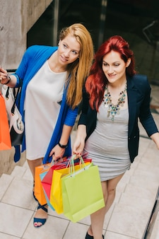 Women walking upstairs with shopping bags