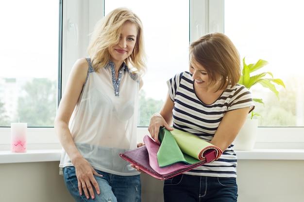 女性はカーテン、家具張り用の布地のサンプルを新しい家で見る。