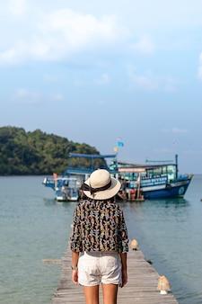 女性海と明るい空の中で木製の橋脚ボートに帽子をかぶる