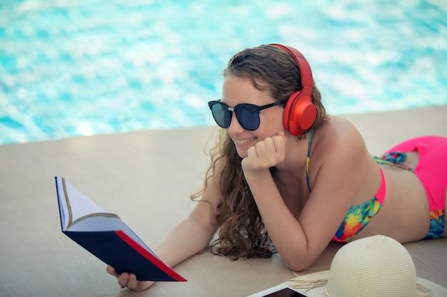 Женщины носят бикини, читают книги и слушают музыку в летнем бассейне отдыха.