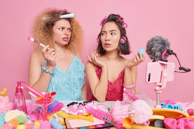 여성들은 드레스를 입고 서로 어리둥절한 표정을 지으며 미용 블로그를 위한 테이블 녹화 비디오에 앉아 화장품을 사용하며 분홍색으로 격리된 현대적인 스마트폰을 사용합니다