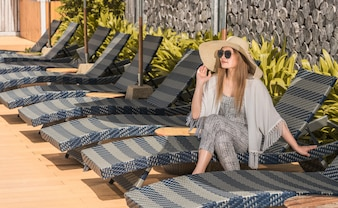 Women wear hat sitting on comfortable chair in pool villa sea view
