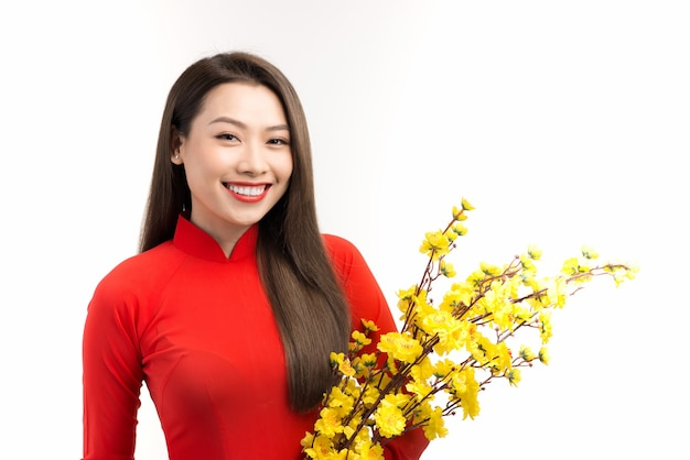 女性はテトの休日に黄色い花のアプリコットでベトナムの伝統のアオザイを着る