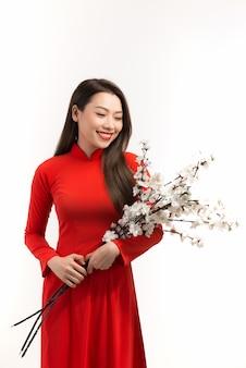 テトの祝日に桃の花を咲かせるベトナムの伝統的なアオザイを着る女性