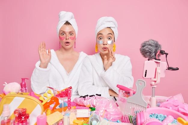 女性は頭に白いバスローブとタオルを着て、スキンケアについてのレビューを作成するビデオを作成し、化粧品を周りに置いてテーブルの近くに美容パッチのポーズを適用します。