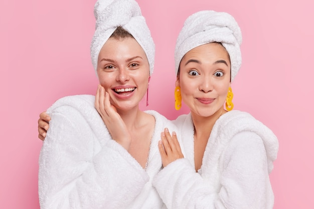 Women wear white bathrobes towels on head spend free time together after beauty and spa procedures isolated on pink