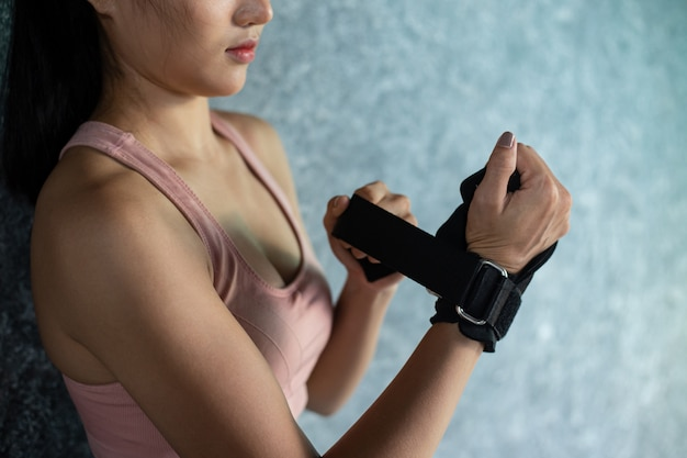 Women wear wristbands to exercise and stand against the wall.