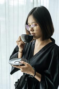 黒いローブを着て、寝室でコーヒーを渡す女性。