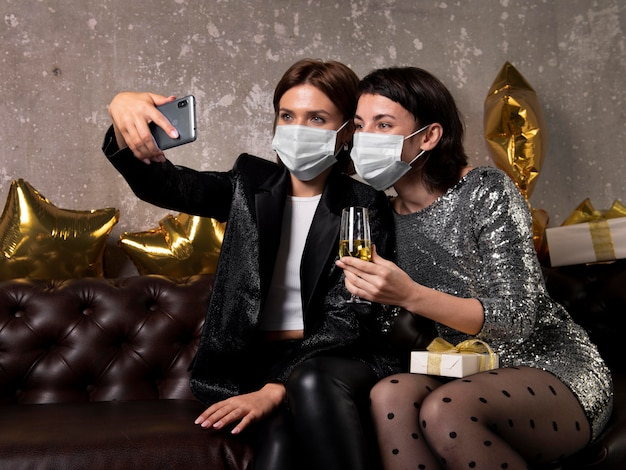 Women wearing face masks taking a selfie
