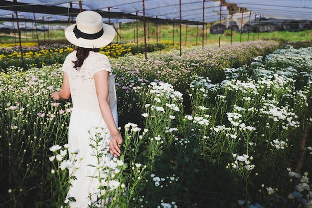 Women wearing hats, walking in the flower garden
