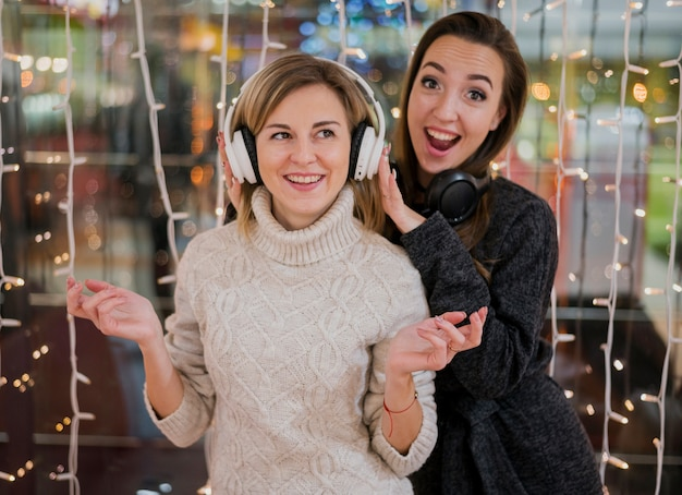 Women wearing headphones having fun around christmas lights