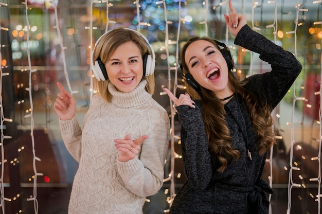 Women wearing headphones near christmas lights