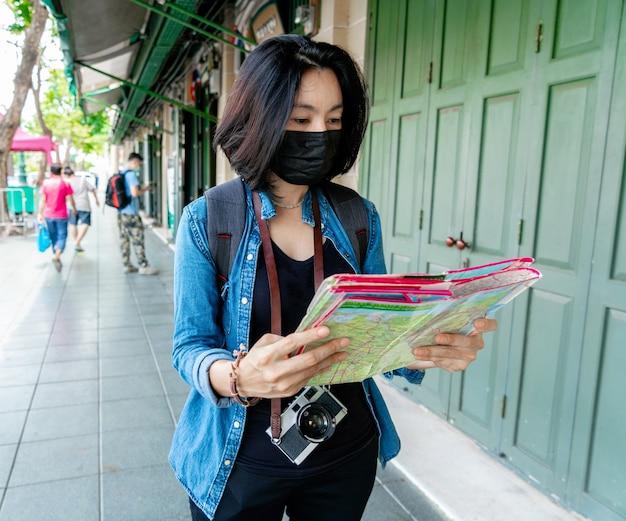 Женщины в маске здоровья смотрят карту для путешествия по городу