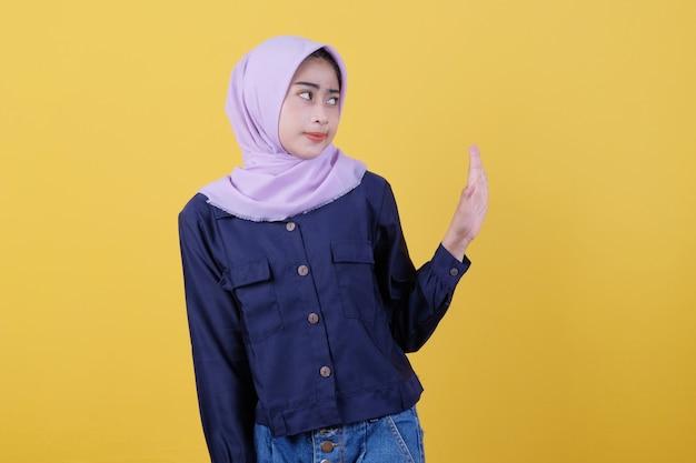 ヒジャーブを身に着けている女性は、制限や拒絶を表現するカジュアルな服を怒って身に着けることによって、彼らの外見を妨げないように求めて、手のひらをストップモーションで真剣に作ります。近づかないで