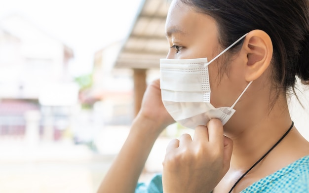 コロナウイルス(covid-19)の流行または大気汚染を保護するためにマスクを着用している女性