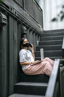 マスクを着用し、階段でノートパソコンを演奏する女性。