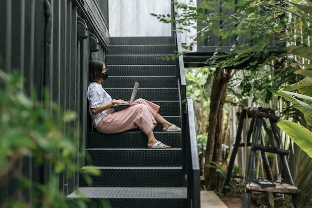 Женщины носят маски и играют в ноутбуки на лестнице.