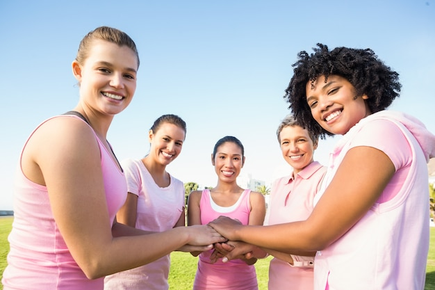 女性が乳がんと手をまとめるためにピンクを着用