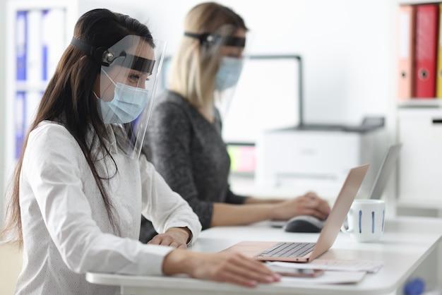 사무실 컴퓨터에서 일하는 보호 마스크와 방패를 착용하는 여성