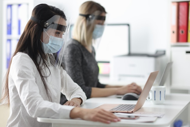 Women wearing protective masks and shields working at computers in office