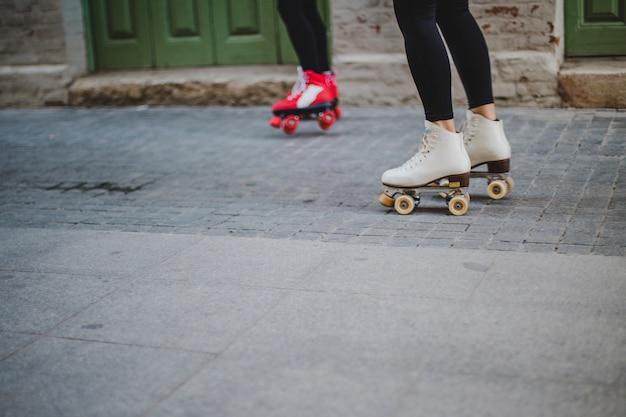 Women wearing rollerskates riding on pavement