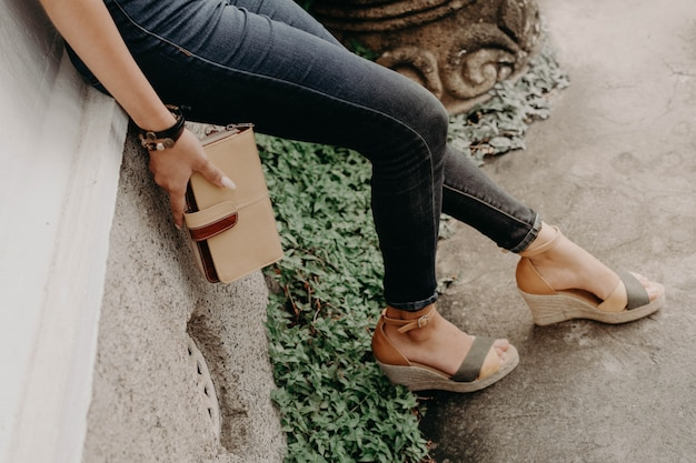 Women wearing sandals or shoes holding a wallet, purse and bag