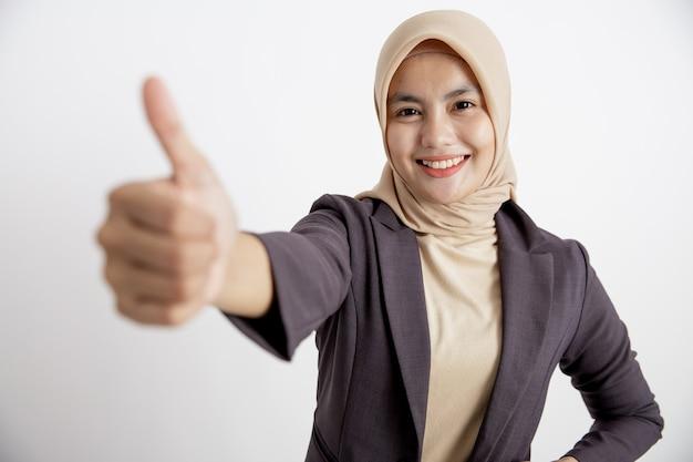 スーツを着ている女性ヒジャーブ良いサインの手のポーズ、フォーマルな孤立した白い壁