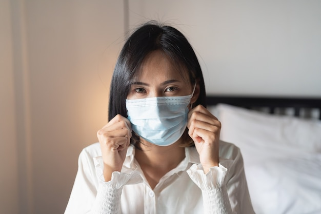 Women wearing surgical mask in the bedroom
