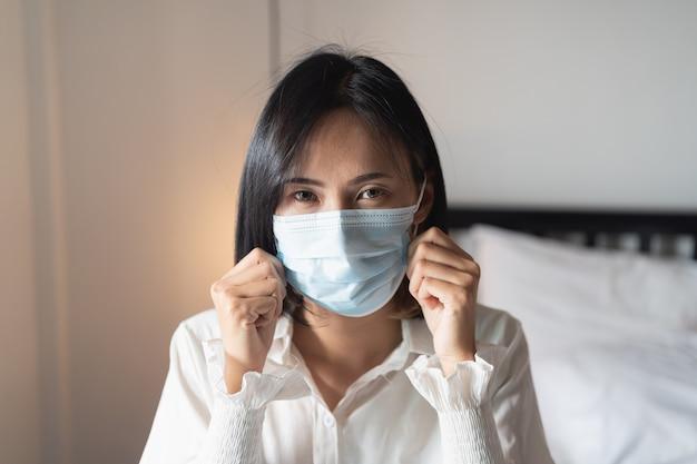침실에서 수술 용 마스크를 착용하는 여성