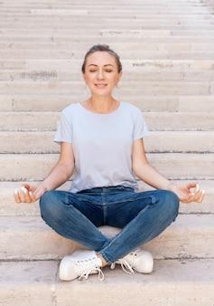 石の階段に足を組んで座って目を閉じて瞑想しているtシャツとジーンズを着ている女性